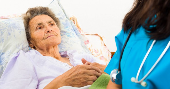 Elderly woman lies in a hospital bed; a nurse sits with her