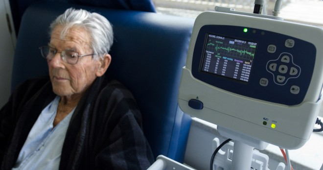 Old man sit connected to a heart monitor