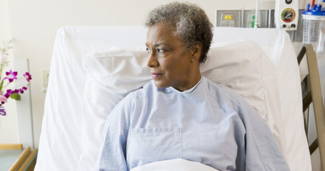 Afro-caribbean woman sitting up in a hospital bed, her expression neutral